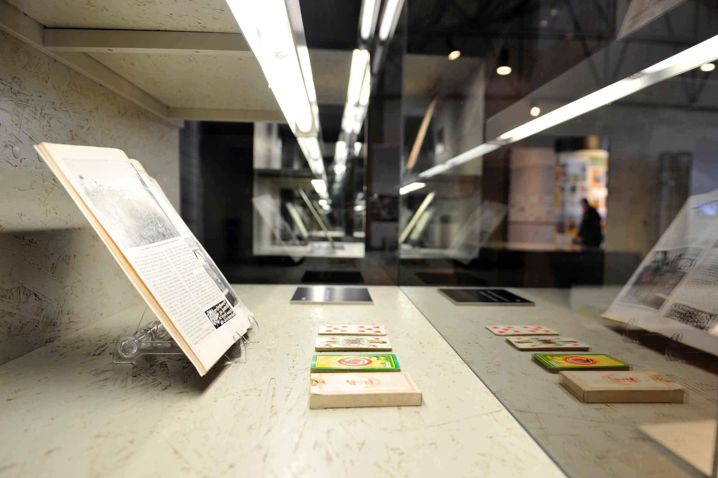 Exponate historischer Bücher und Karten ausgestellt in einer Vitrine